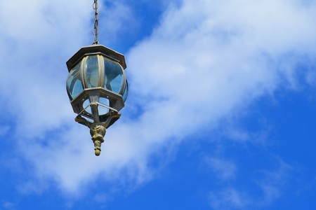 Decorated metal lantern against the blue cloudy sky. 免版税图像