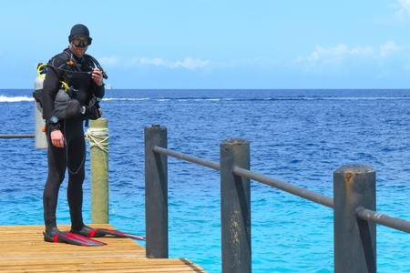 Scuba diver on the wooden pier prepared to jump into the sea azure water. 免版税图像