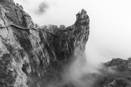 walkway  built along the   cliff, surrounded by fog Stock Photo