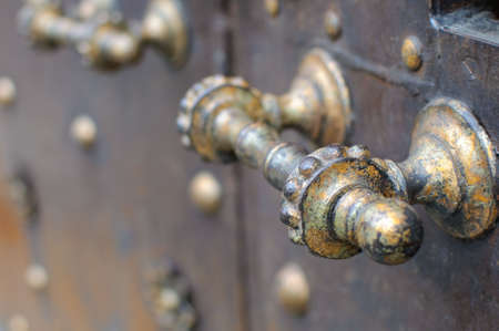tarnished: A rustic metal doorhandle.
