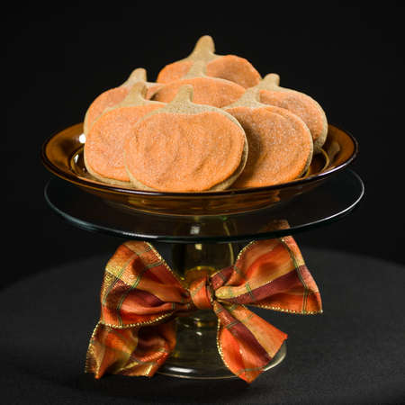Homemade pumkin cookies on isolated black background. Stock Photo