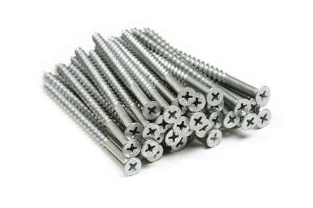 pile of four inch wood screws on isolated white background.
