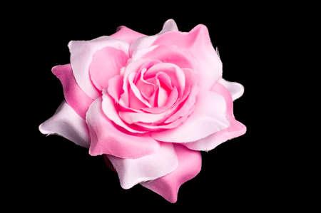 Een roze bloem haar clip voor vrouwen op geïsoleerde zwarte achtergrond. Stockfoto