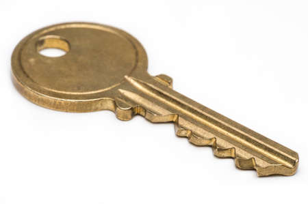 Yellow brass key on isolated white background. Stock Photo