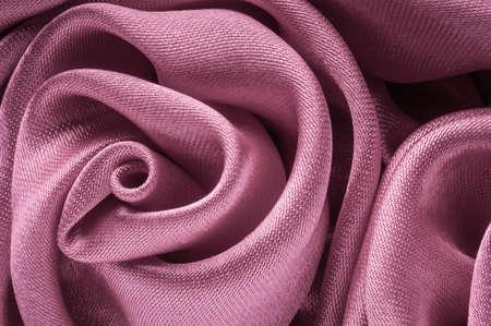 Close up of shiny light purple fabric rose shaped flower.