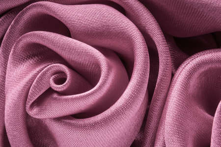 Close up of shiny light purple fabric rose shaped flower.