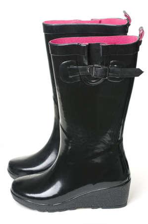 zwarte rubberen laarzen op een witte achtergrond met roze binnenkant