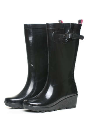 black rubber boots on white background with pink insides