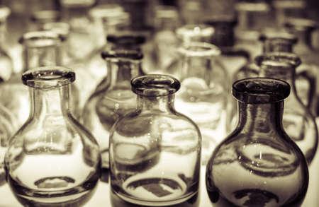 An assortment of empty glass bottles on light box.