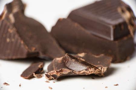 Macro shot of dark chocolate pieces on white. Stock Photo