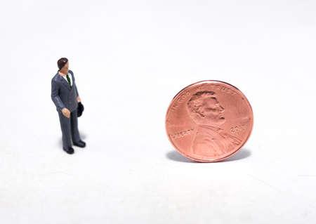 Kleine plastic mensen kijken naar een cent