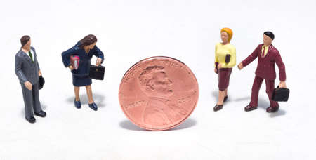 Small plastic people looking at a penny Stock Photo