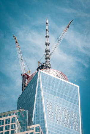 Top of cloudy Freedom tower with crane