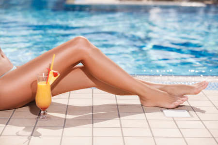 Beautiful tanned legs. Close-up of female legs and cocktail with a swimming pool on the background photo
