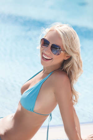 Shiny beautiful girl. Portrait of beautiful young women in bikini smiling on camera with a swimming pool on the background photo