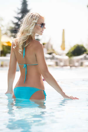 Beauty in pool. Rear view of beautiful young women in bikini standing in pool and smiling photo