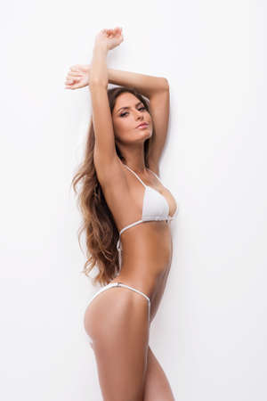 lingerie model: Beautiful woman in white bikini. Side view of attractive young woman in bikini looking at camera while standing isolated on white
