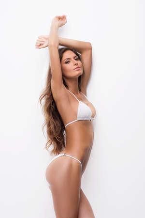 bikini wear: Beautiful woman in white bikini. Side view of attractive young woman in bikini looking at camera while standing isolated on white