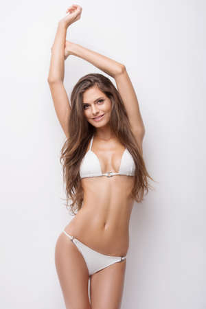Beauty in white bikini. Attractive young woman in bikini keeping her arms raised and looking at camera while standing isolated on white Stock Photo