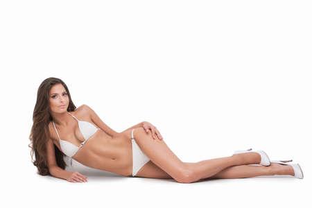 bikini wear: Beauty in white bikini. Beautiful young woman in white bikini lying on side and looking at camera while isolated on white