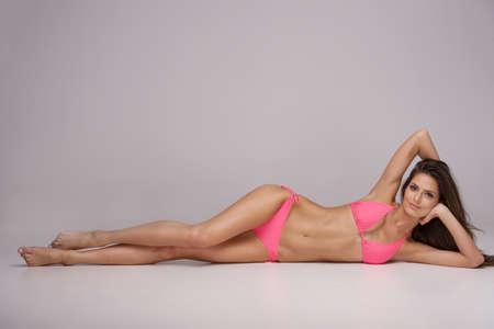 bikini wear: Beauty in pink bikini. Attractive young woman in bikini lying on side and looking at camera while isolated on grey