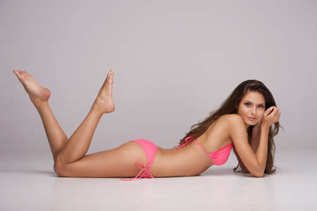 Beauty in pink bikini. Attractive young woman in bikini lying front and looking at camera while isolated on grey