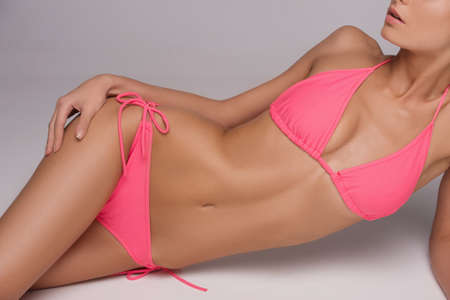 Beautiful woman in pink bikini. Cropped image of attractive young woman in bikini lying on side while isolated on grey photo