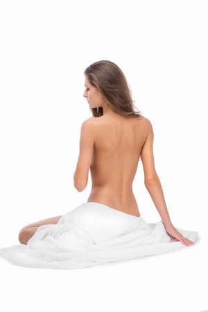 naked woman sitting: Naked beauty. Rear view of attractive naked woman sitting on the floor and covering body with white cloth while isolated on white