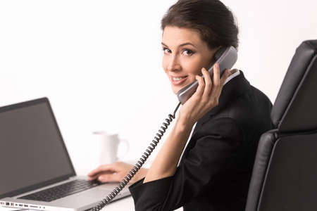 Talking at phone. Confident middle-aged businesswoman sitting at her working place and looking over shoulder photo