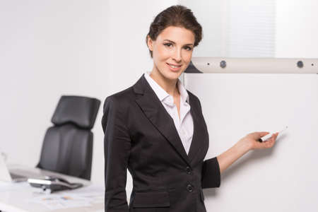 Businesswoman near whiteboard. Confident middle-aged businesswoman pointing whiteboard and looking at camera photo