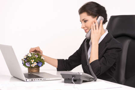 Talking at phone. Confident middle-aged businesswoman sitting at her working place talking at phone Stock Photo - 21905907