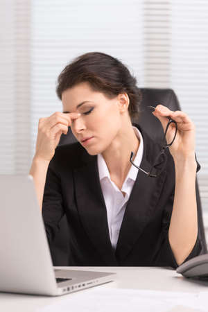 tired eyes: Tired businesswoman. Tired middle-aged businesswoman sitting at her working and keeping her eyes closed