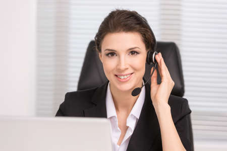 customer service representative: Customer service representative. Confident middle-aged woman in headphones sitting at her working place and smiling Stock Photo