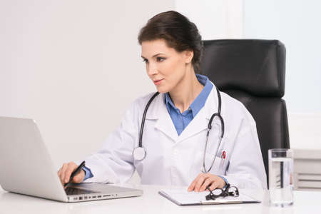 Confident doctor. Confident middle-aged female doctor sitting at her working place and working at the computer photo