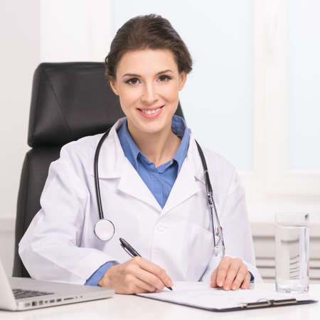 Confident doctor. Confident middle-aged female doctor sitting at her working place and writing something at the note pad photo