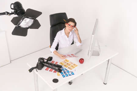 top clothing: Creative businesswomen. Top view of confident middle-aged businesswoman sitting at her working place and looking at camera Stock Photo