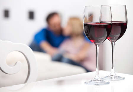 Romantic moments. Beautiful middle aged couple sitting on the floor and holding hands while two glasses of red wine standing on the foreground photo