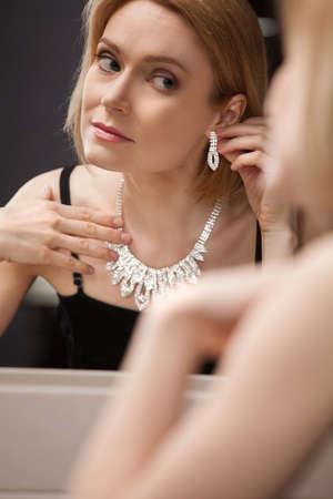 beautiful middle aged woman: Beautiful mature woman. Beautiful middle aged woman putting on the earrings