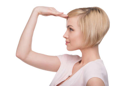 gestos de la cara: Hermosa mujer rubia. Vista lateral de la joven y atractiva mujer de cabello rubio señalando y mirando a otro lado mientras aislados en blanco