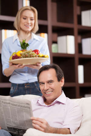 Happy mature couple. Cheerful middle aged man holding newspaper and smiling while her wife standing at the background and holding a plate with fruits photo