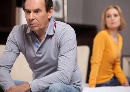 problemas familiares: Dificultades de relación. Deprimido pareja de mediana edad sentados en el sofá