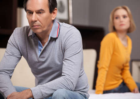 relationship problem: Relationship difficulties. Depressed middle aged couple sitting on the sofa