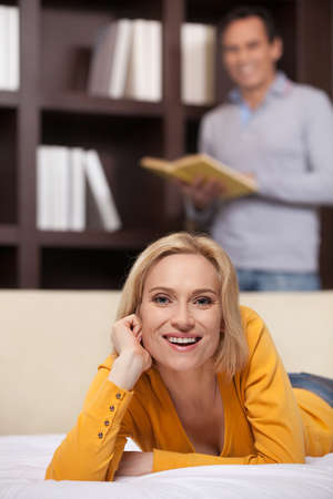 Couple relaxing at home. Cheerful middle aged woman lying on the sofa and smiling while her husband choosing a book to read at the background photo