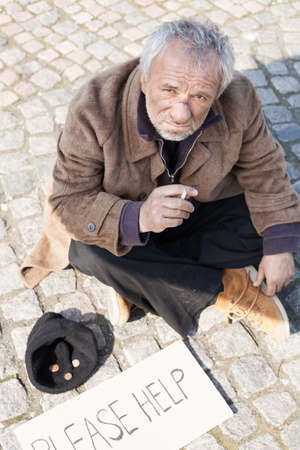 tramp: Tramp. Depressed senior man in dirty wear sitting on the floor outdoors and smoking