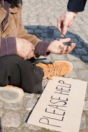 tramp: Tramp. Close-up of man giving money to tramp Stock Photo