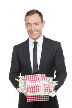Expensive gift. Happy young man in formalwear holding a gift box full of money while standing isolated on white photo