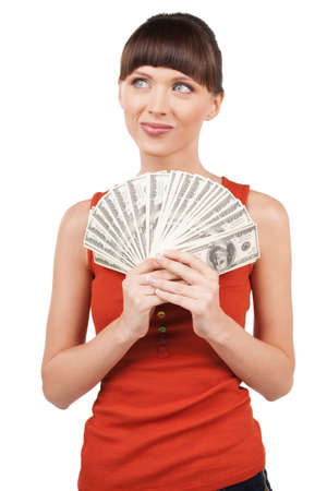 woman holding money: Rich woman. Thoughtful young woman holding money while standing isolated on white Stock Photo