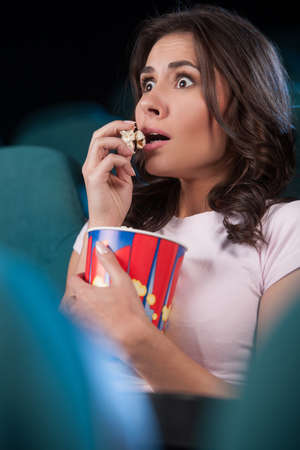 Women at cinema. Beautiful young women eating popcorn while watching movie at the cinema photo