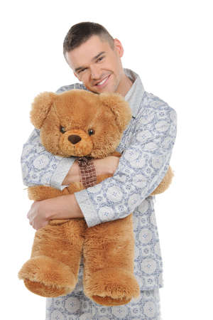 Man with teddy bear. Young man in pajamas hugging teddy bear and smiling while standing isolated on white photo