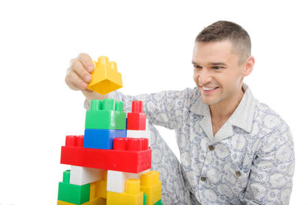 Big baby. Young man in pajamas playing toys while sitting isolated on white Stock Photo - 21986101